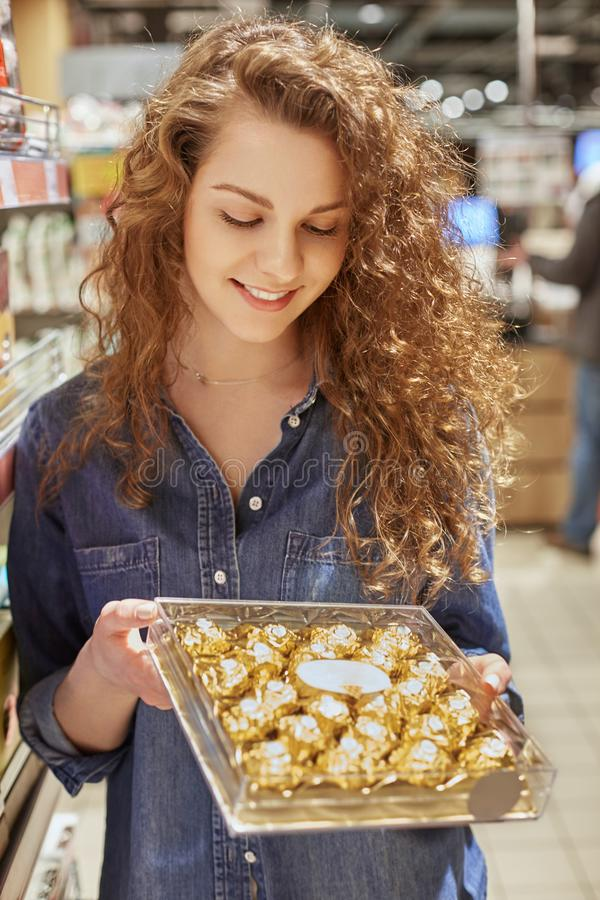Vertical shot of pleasant looking pleased female holds box with delicious chocolate candies, chooses dessert to drink tea or coffe stock photography
