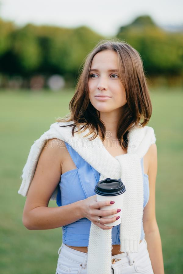 Vertical shot of pleasant looking young European female looks pensively aside, dressed in casual t shirt, sweater on shoulders, ho. Lds takeaway coffee, stands royalty free stock photos