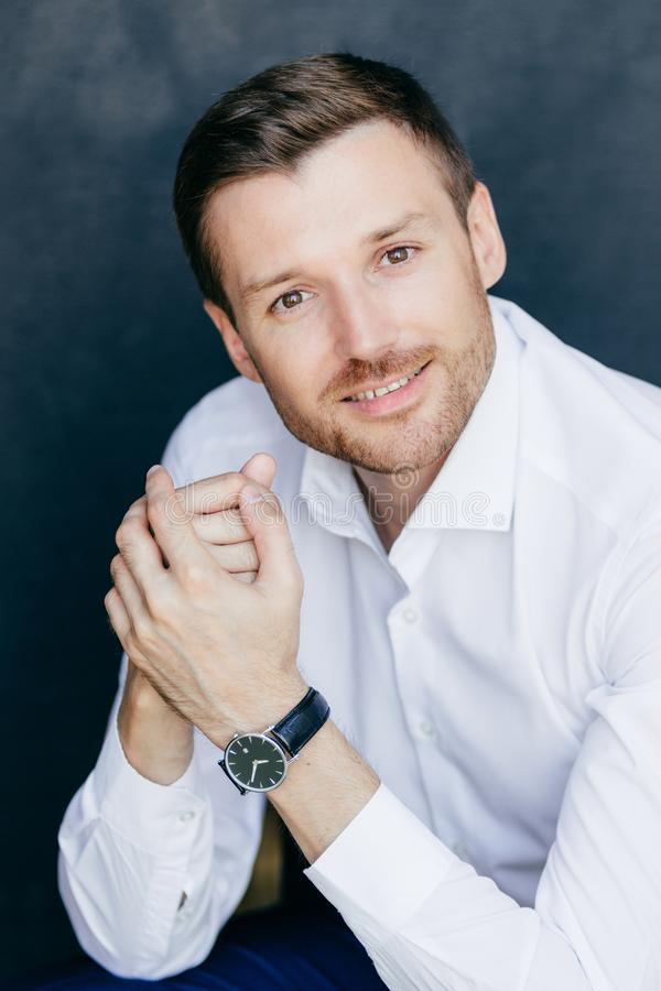 Vertical shot of pleased unshaven male entrepreneur, has bristle. Dark hair, keeps hands together, dressed in elegant white shirt, looks at camera with royalty free stock photography