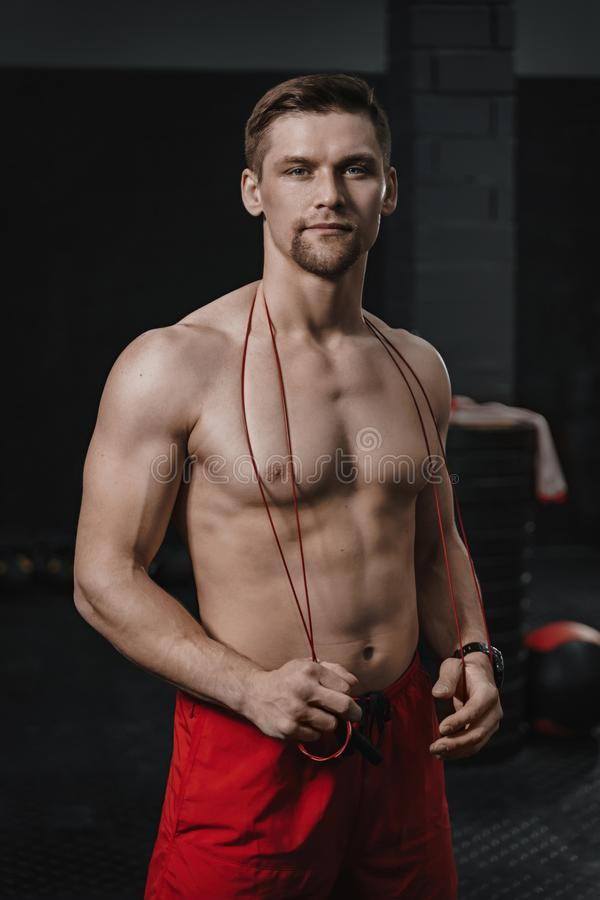 Vertical shot portrait of young handsome shirtless athlete at the crossfit gym stock images