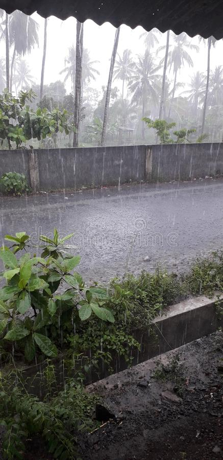 Vertical shot of the pouring rain in the street of Manado City in Indonesia stock images