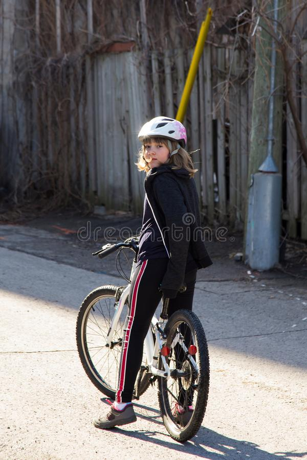 Vertical shot of pretty little girl with dark blond windswept hair sitting on her bicycle royalty free stock images