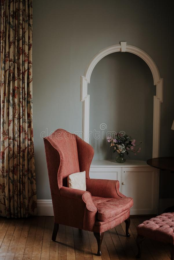 Vertical shot of a red armchair, a white stand with a flower on it in a room. A vertical shot of a red armchair, a white stand with a flower on it in a room royalty free stock photos