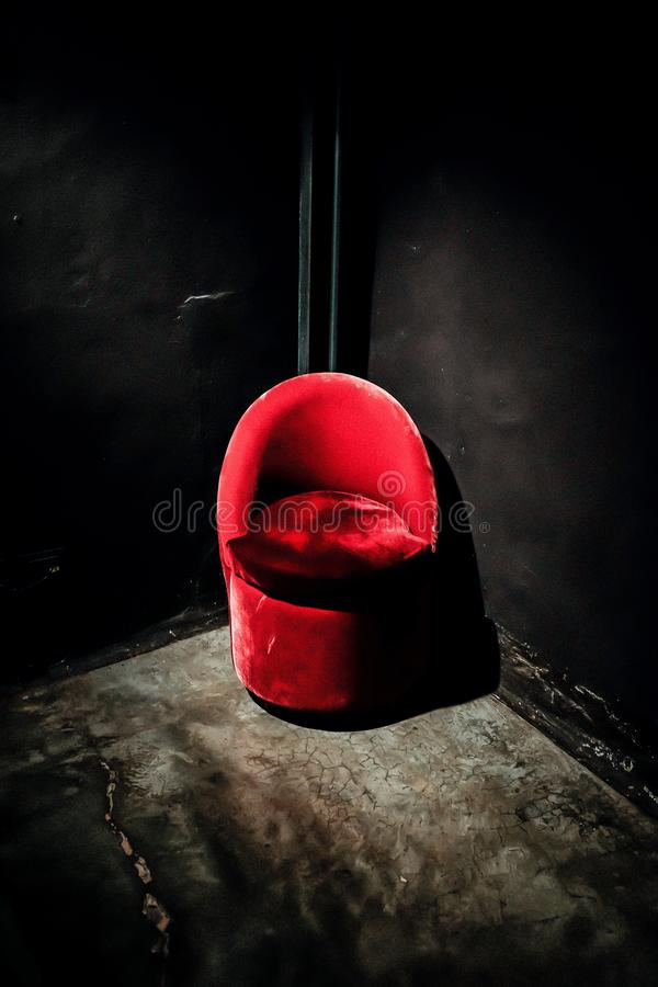 Vertical shot of a red suede chair in the corner of black walls. A vertical shot of a red suede chair in the corner of black walls royalty free stock images