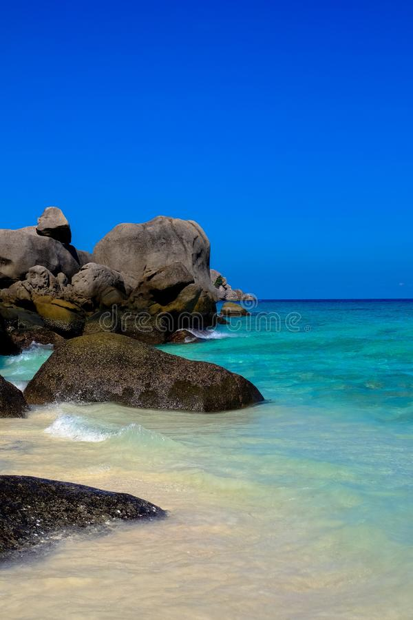 Vertical shot of rocks near the clear water sea with blue sky in the background. A vertical shot of rocks near the clear water sea with blue sky in the royalty free stock images