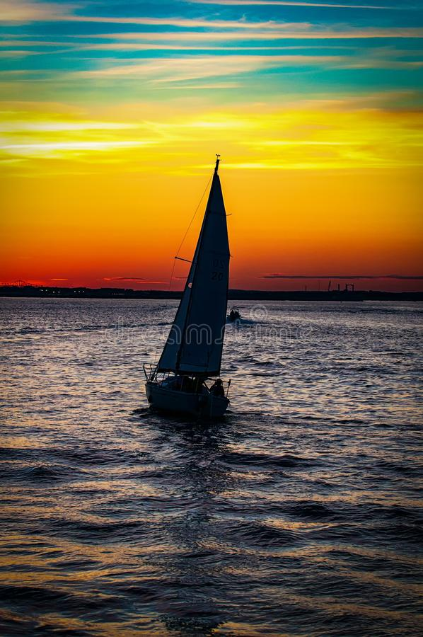 Vertical shot of a sailing ship flowing under the breathtaking sunset stock image