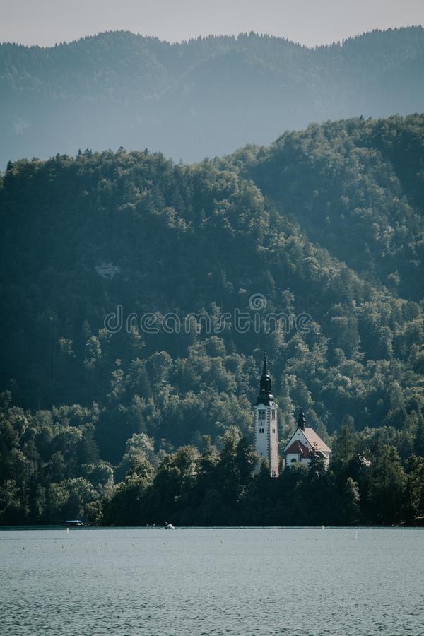 Vertical shot of sea with a house surrounded by trees in the distance near forested mountains. A vertical shot of sea with a house surrounded by trees in the royalty free stock images