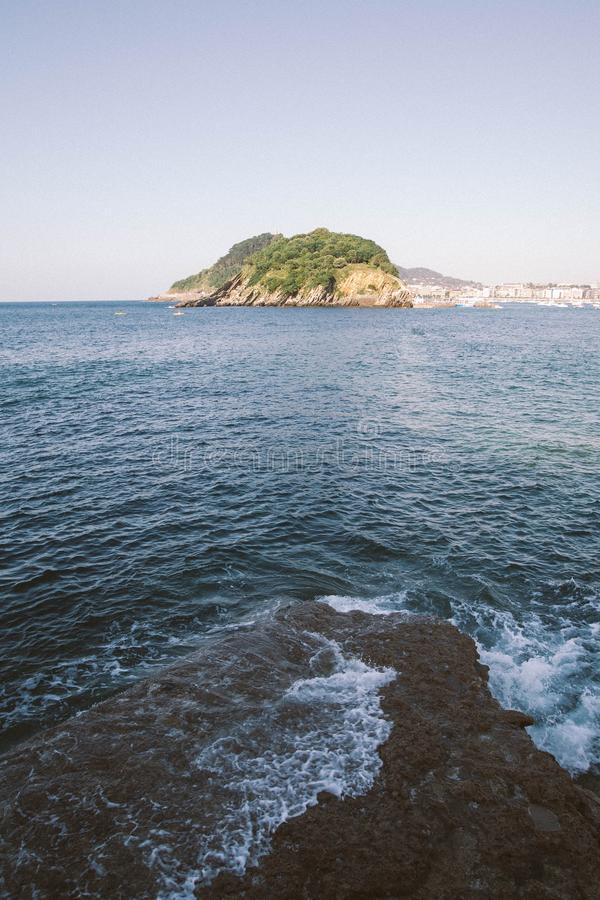 Vertical shot of sea waves hitting the rock with a mountain in the distance under a clear sky. A vertical shot of sea waves hitting the rock with a mountain in royalty free stock photography