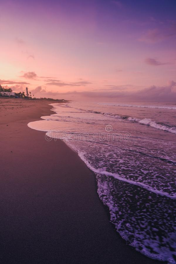 Vertical shot of the sea waves under the beautiful purple sky captured in Canggu, Bali. A vertical shot of the sea waves under the beautiful purple sky captured stock photography