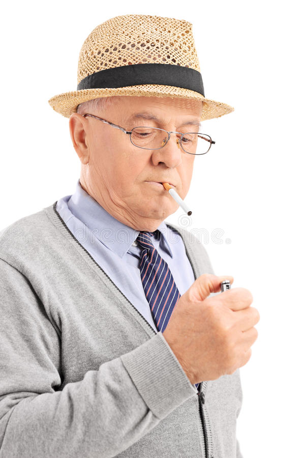 Vertical shot of a senior lighting up a cigarette. Isolated on white background stock photography