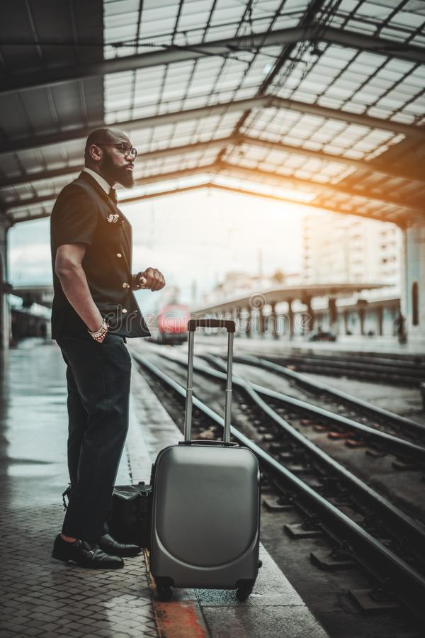 A black guy waiting for the train. A vertical shot of a serious adult African man entrepreneur standing on an indoor railway platform and looking aside after stock photos