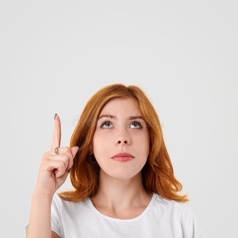 Vertical shot of serious focused European young female points upwards with fore finger, shows blank space for your advertising con stock images