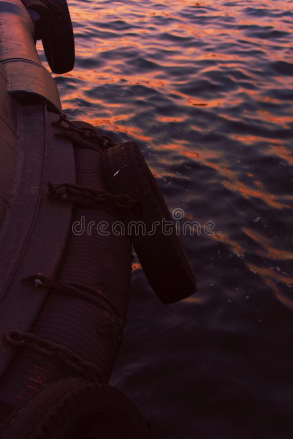 Vertical shot of the side of an inflatable boat sailing on the body of water at sunset. A vertical shot of the side of an inflatable boat sailing on the body of stock photos