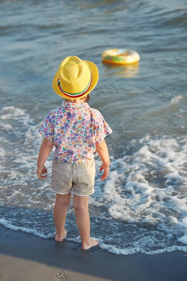 Vertical shot of small fashionable girl stands back, wears summer hat, blouse and shorts, admires sea, plays alone, breathes fresh stock photo