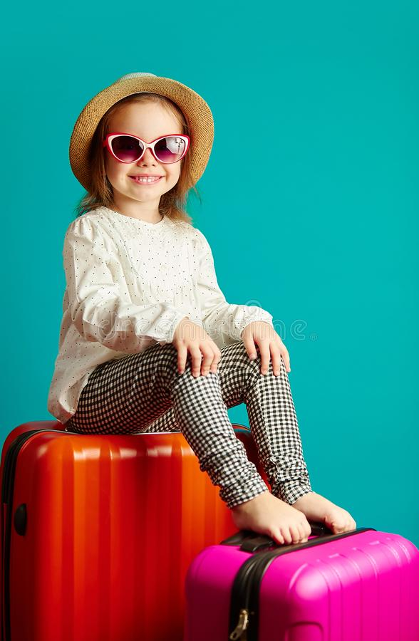 Vertical shot of smiling little girl in straw hat and sunglasses sitting on suitcases, portrait of beautiful child going royalty free stock photography