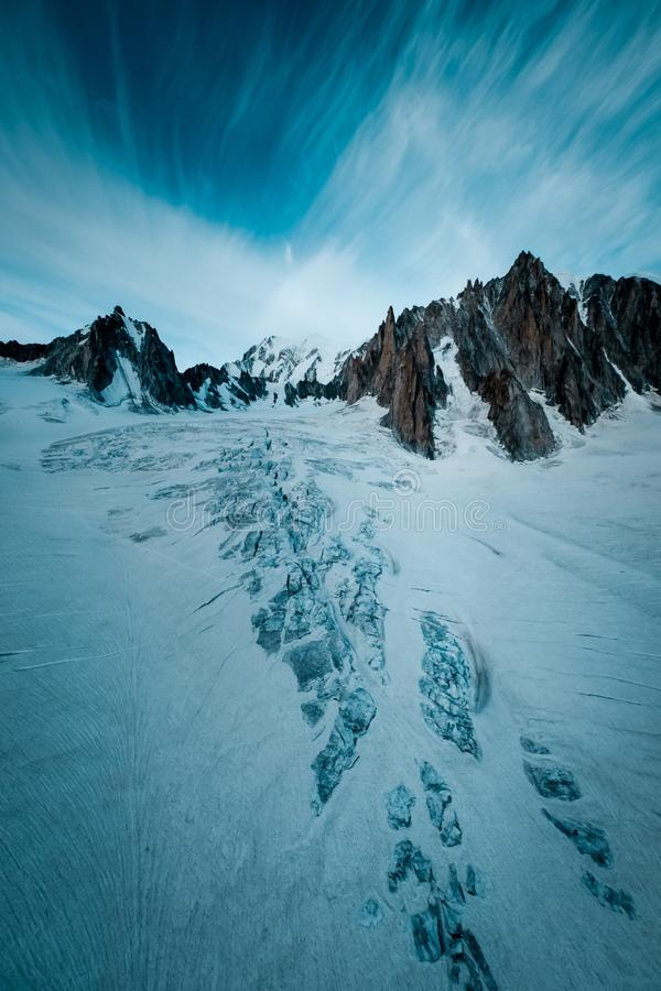 Vertical shot of a snowy hill with mountains in the distance under a cloudy sky. A vertical shot of a snowy hill with mountains in the distance under a cloudy stock photography