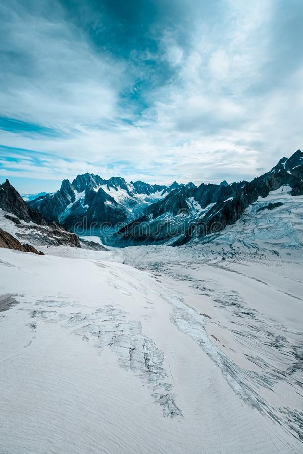 Vertical shot of a snowy hill with mountains in the distance under a cloudy sky. A vertical shot of a snowy hill with mountains in the distance under a cloudy royalty free stock image
