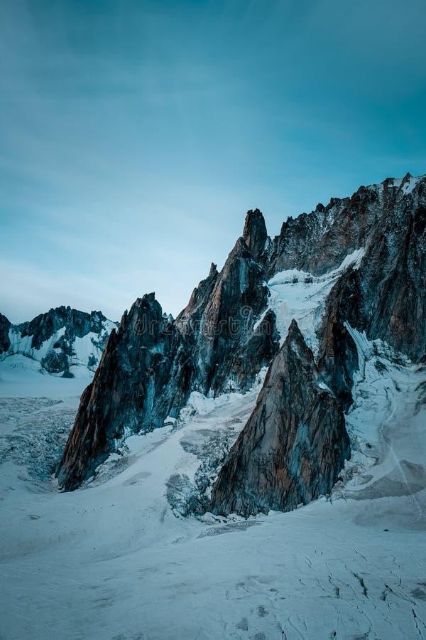Vertical shot of a snowy hill near mountain under a blue sky. A vertical shot of a snowy hill near mountain under a blue sky royalty free stock photos
