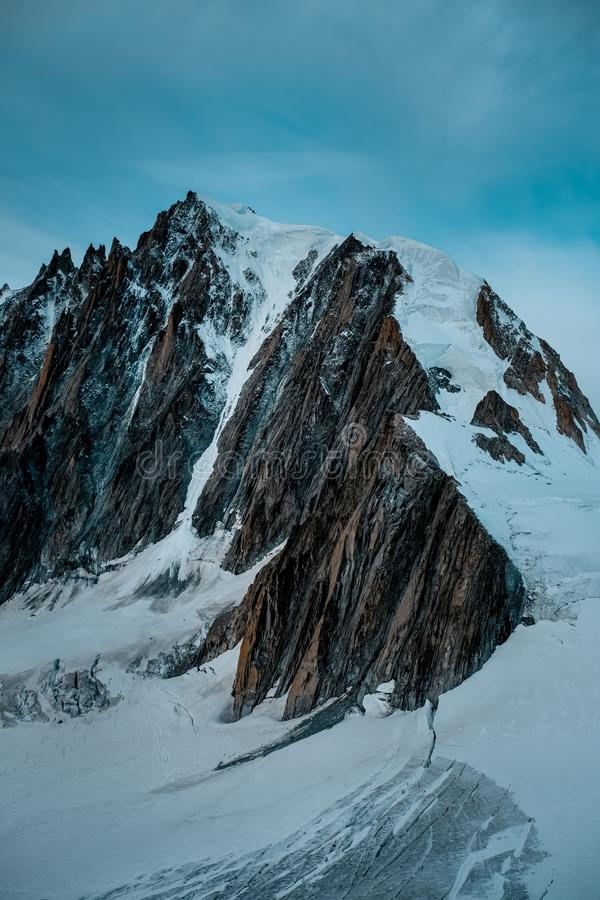 Vertical shot of a snowy mountain with a blue sky in the background. A vertical shot of a snowy mountain with a blue sky in the background royalty free stock photos
