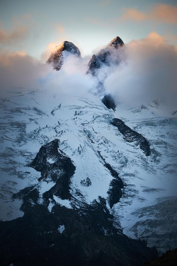 Vertical shot of a snowy mountain in the clouds at daytime. A vertical shot of a snowy mountain in the clouds at daytime stock photos