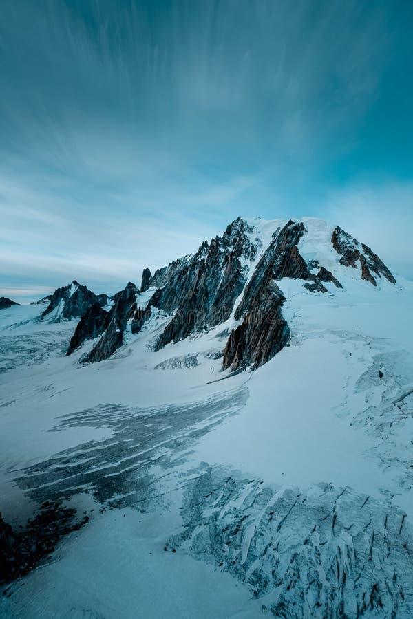 Vertical shot of snowy mountains under a dark blue sky. A vertical shot of snowy mountains under a dark blue sky royalty free stock photo