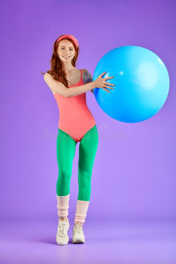 Vertical shot of sporty cute ginger girl training pectorals. Full lenght vertical shot of sporty cute ginger girl making exercises with blue fitness ball, making stock photography