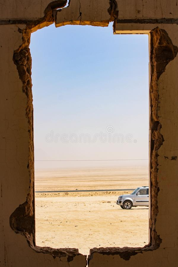 Vertical shot of a square hole on a wall with a view of a car parked in the desert royalty free stock photo