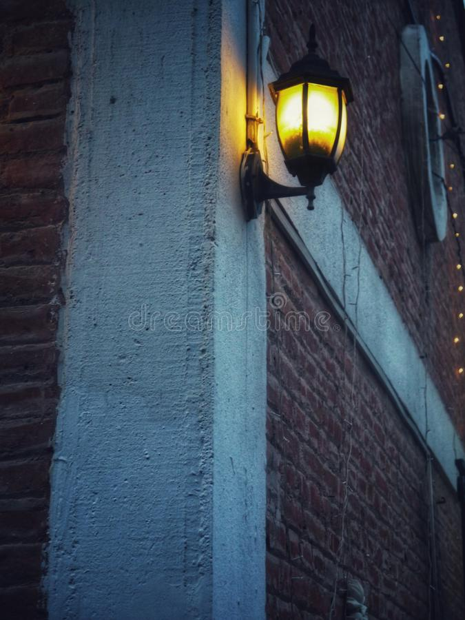 Vertical shot of a street lamp attached to a building at midnight. A vertical shot of a street lamp attached to a building at midnight royalty free stock images