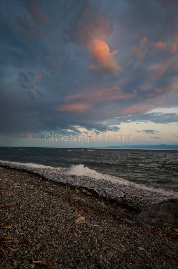 Vertical shot of sunset colored storm clouds over Juan de Fuca Strait, waves breaking on the beach in the forground. Along the waterfront near Victoria, BC stock photos