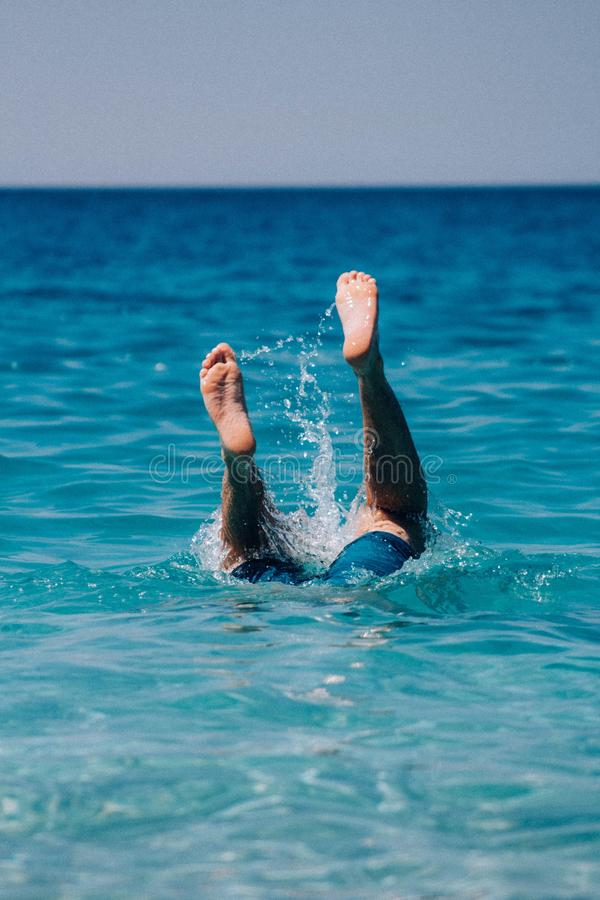 Vertical shot of a swimming person`s feet in the water. A vertical shot of a swimming person`s feet in the water stock image
