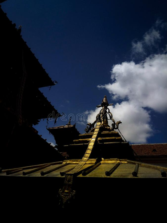 Vertical shot of a temple roof under a dark blue sky. A vertical shot of a temple roof under a dark blue sky stock photography