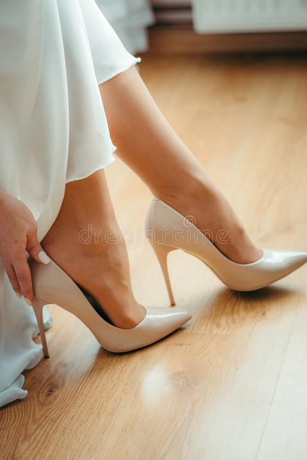 Vertical shot of the tender hands of the bride are putting on the white wedding high heels. royalty free stock image