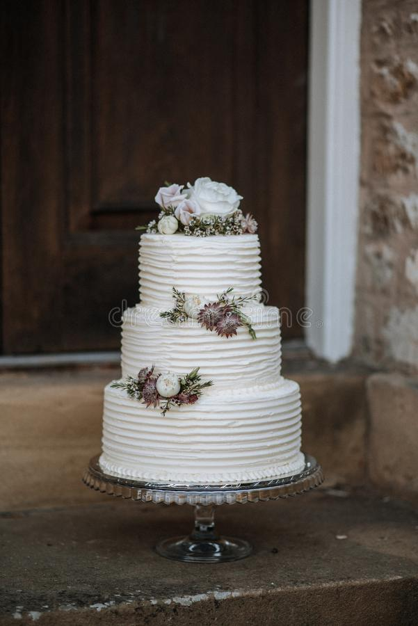 Vertical shot of a three-layer wedding cake decorated with flowers on a silver platter. A vertical shot of a three-layer wedding cake decorated with flowers on a stock photography