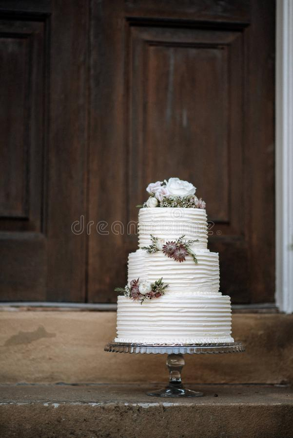 Vertical shot of a three-layer wedding cake decorated with flowers on a silver platter. A vertical shot of a three-layer wedding cake decorated with flowers on a royalty free stock photography