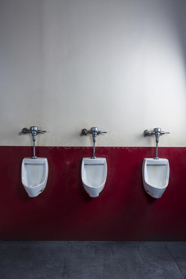 Vertical shot of three unmanned urinals on a red and cream coloured wall. Vertical shot of three side by side urinals royalty free stock photos