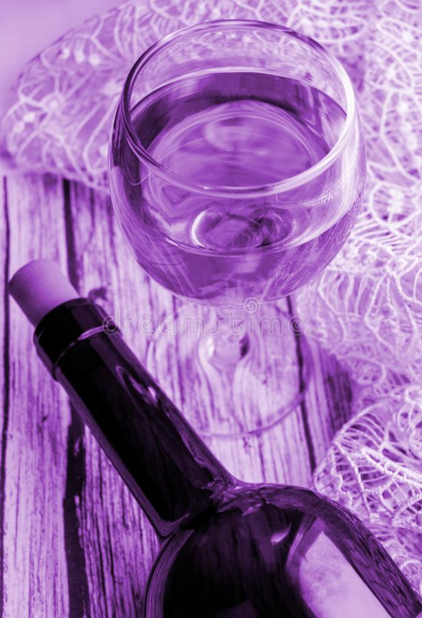 Vertical shot with tinted lilac effect - a Glass of wine and a bottle on a wooden table. Top view, flat.  stock photos