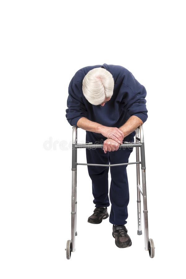 Tired Elderly Man Resting On His Walker Isolated On White. Vertical shot of a tired elderly man resting on his walker with his head down isolated on white with royalty free stock photos
