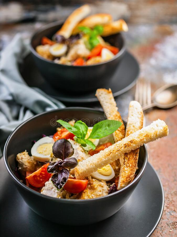 Vertical shot of two servings of Caesar salad with chicken, quail egg, cherry tomatoes, croutons and basil in dark blue bowls on a. Rusty background royalty free stock photography