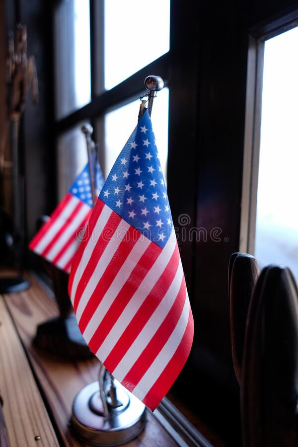 Vertical shot of the U.S. flags placed on a table beside a window. A vertical shot of the U.S. flags placed on a table beside a window royalty free stock images