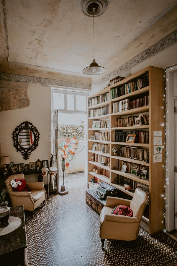 Vertical shot of a vintage room`s interior with a bookshelf and white armchairs. A vertical shot of a vintage room`s interior with a bookshelf and white royalty free stock photography
