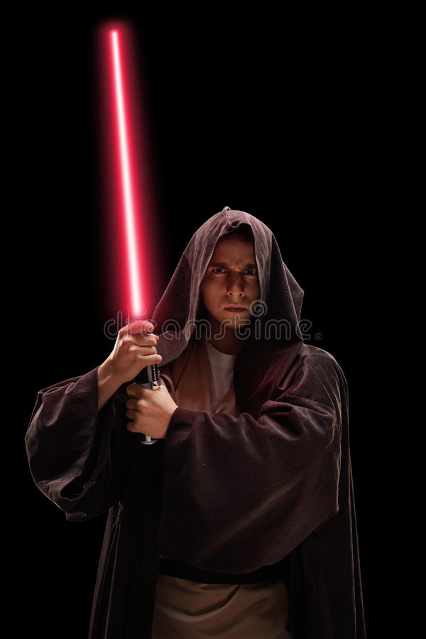 Vertical shot of a warrior with laser sword. Vertical shot of a male warrior with red laser sword on black background stock photos