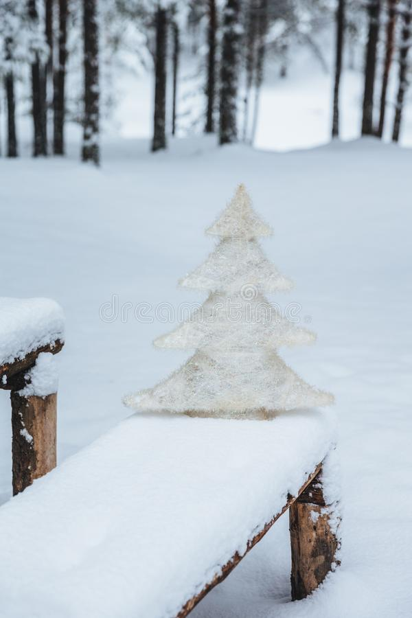 Vertical shot of white artificial fir tree on bench covered with snow, in winter frosty forest. Holidays decoration. Season concep. T. Holiday. Wonderful winter stock photography
