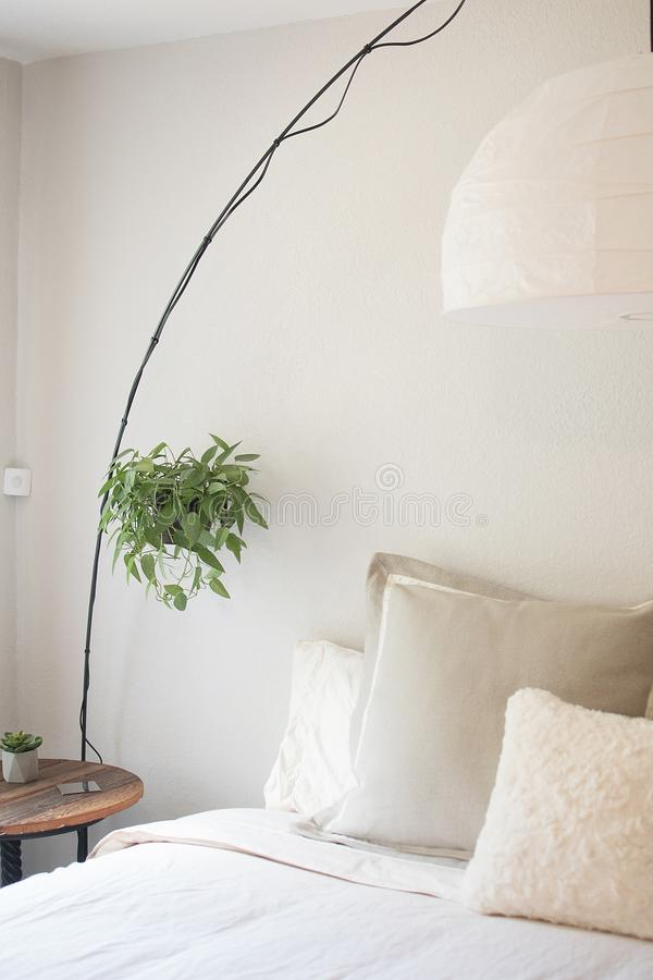 Vertical shot of a white bed with pillows and a round wooden bed next to it with a hanging plant royalty free stock images
