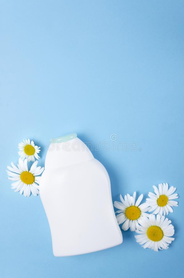 Vertical shot of white plastic bottle and white flowers on the blue blank background, empty space for design stock photo