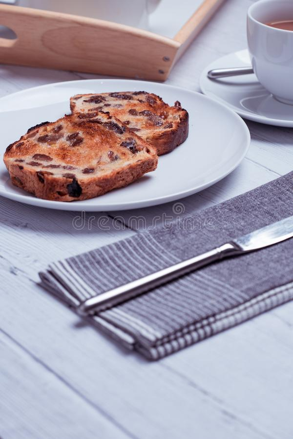 Vertical shot of a white plate with tasty raisin bread, tea, table knife on a white wooden surface. A vertical shot of a white plate with tasty raisin bread, tea stock photo