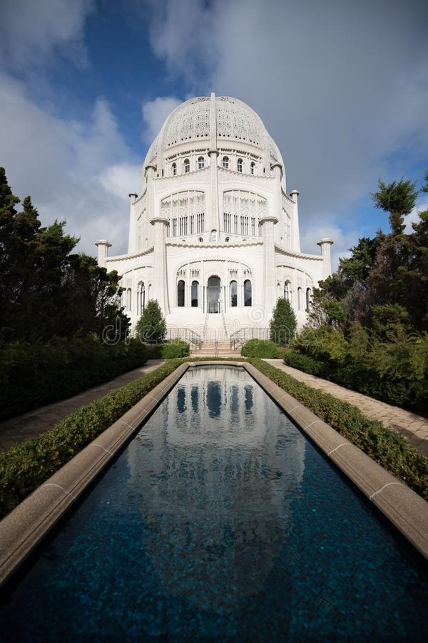 Vertical shot of a white tall palace with a vertical pool in front of it and greenery stock images