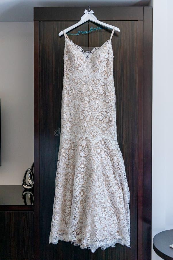 Vertical shot of a white wedding dress hanged on the wooden door. A vertical shot of a white wedding dress hanged on the wooden door stock image