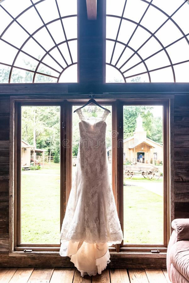 Vertical shot of a white wedding dress hanging in front of a window. A vertical shot of a white wedding dress hanging in front of a window royalty free stock images
