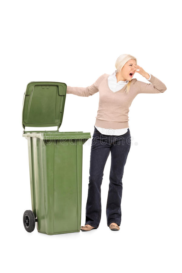 Vertical shot of a woman opening a stinky trash can royalty free stock images
