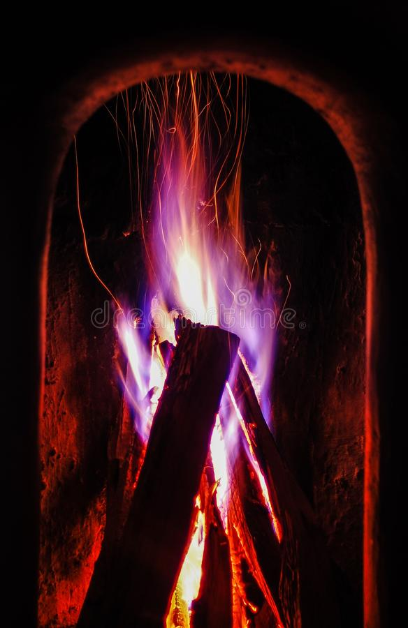 Vertical shot of wood burning with purple and blue fire in a dark room. A vertical shot of wood burning with purple and blue fire in a dark room stock photo